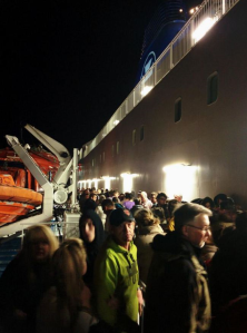 Passengers waiting on the open decks for further information following the fire in a passenger cabin